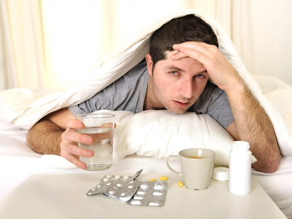 exhausted young Man in bed with coffee, water and tablets suffering hangover and headache
