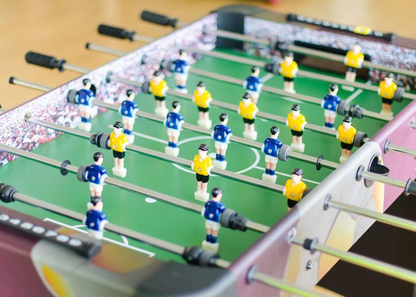 Calcio balilla con giocatori gialli e blu