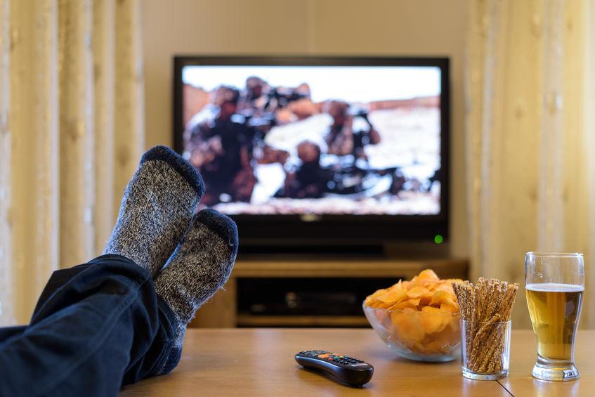 Gambe su un tavolino con sullo sfondo la TV