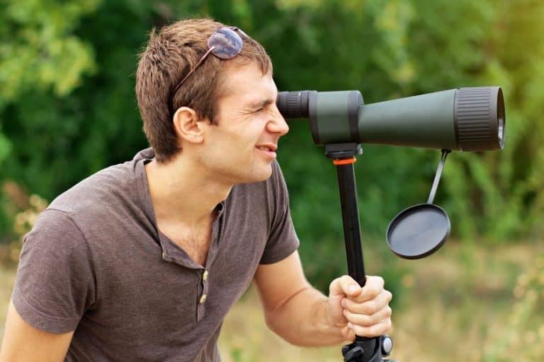 Uomo che usa un telescopio terrestre