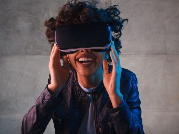 Cheerful young woman touching the virtual reality goggles on her head.