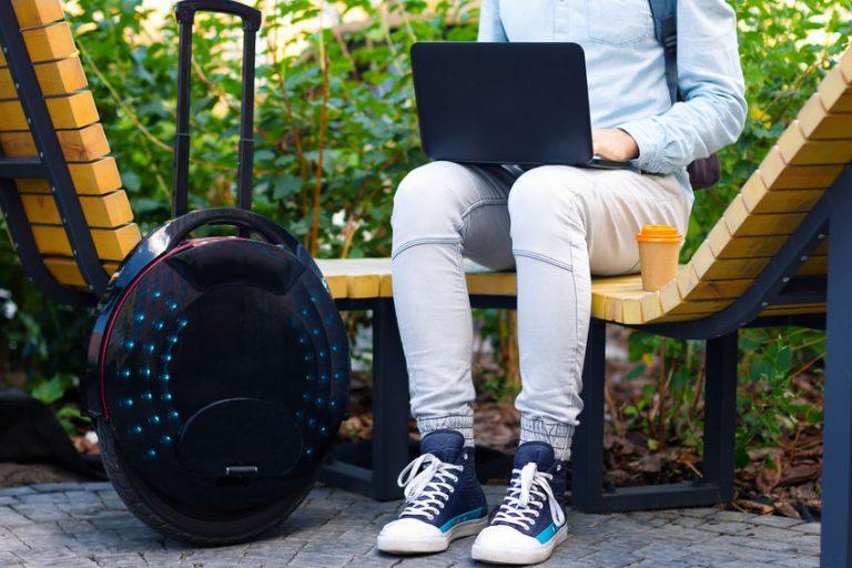 Persona seduta su una panchina di fianco a un monociclo elettrico