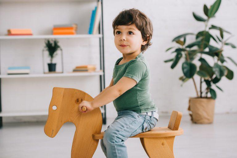 Bimbo seduto sul cavallo a dondolo in legno