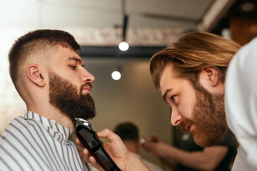 Barbiere che regola la barba a un cliente