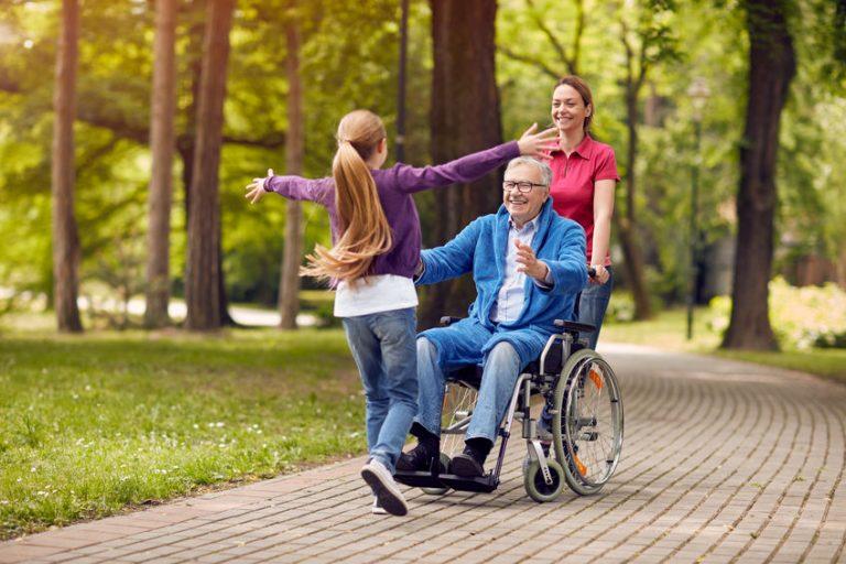 Bambina che va a abbracciare il nonno sulla sedia a rotelle