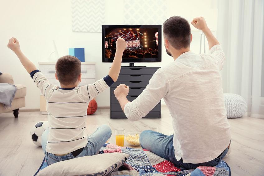 Padre e figlio davanti a una TV esultando