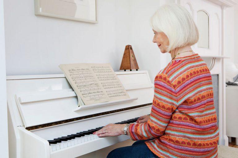Donna che suona al pianoforte con metronomo