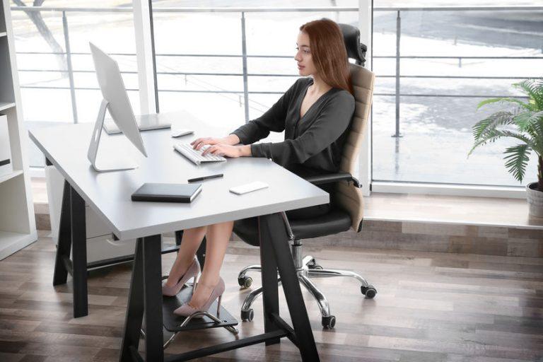 Donna alla scrivania che usa un poggiapiedi