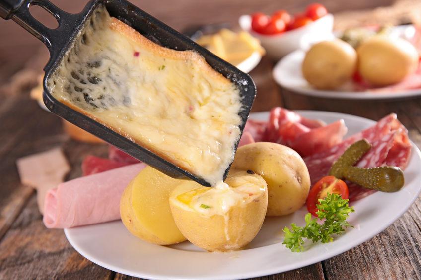 Formaggio fuso con una raclette versato sulle patate
