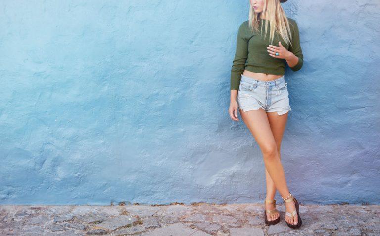 Donna in pantaloncini appoggiata a una parete