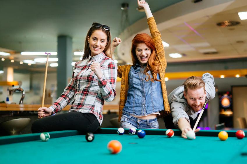Tre giovani che si divertono a giocare a biliardo