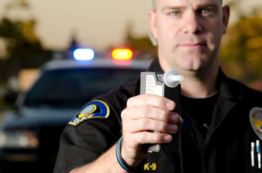 Poliziotto con etilometro in mano