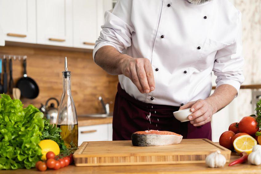 Cuoco che sala il salmone sul tagliere