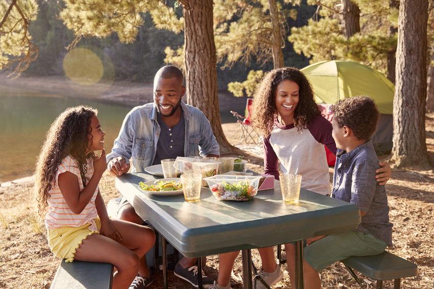 Famiglia che mangia mentre fa campeggio