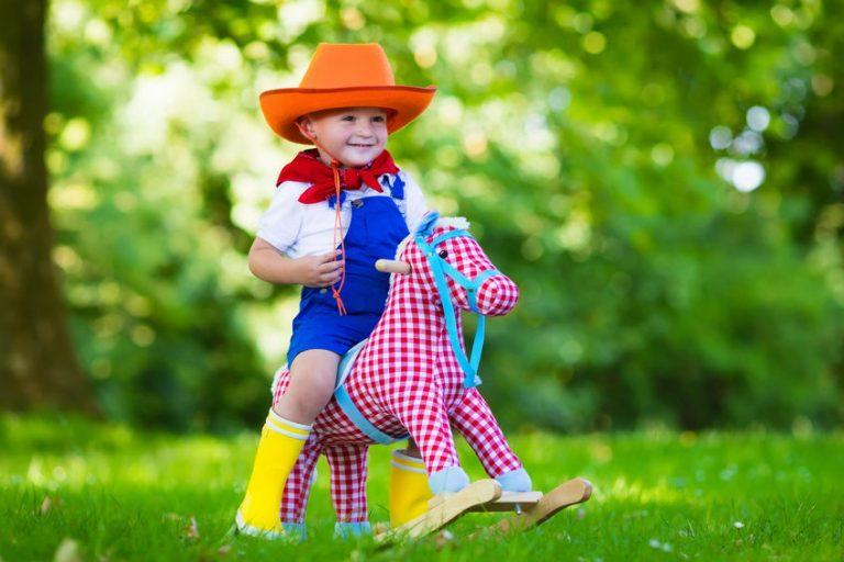Bambino su un cavallo a dondolo in giardino
