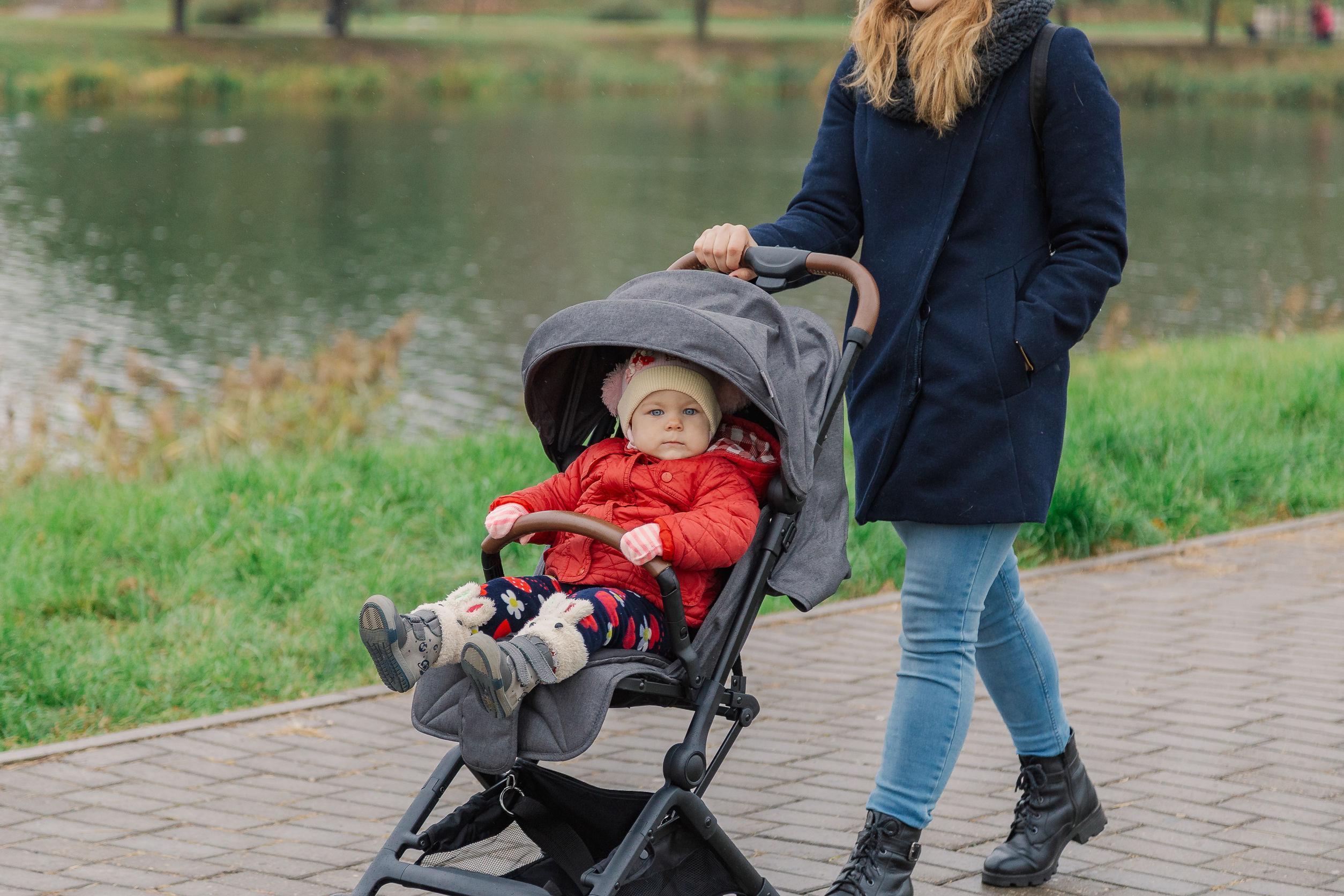 Donna che porta il bambino nel passeggino