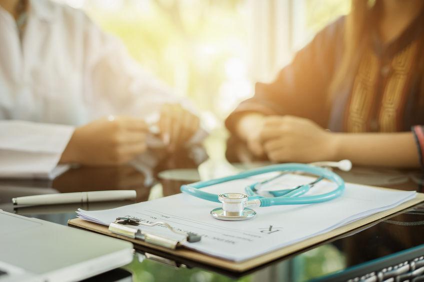 Stetoscopio su una cartella clinica e due persone sullo sfondo