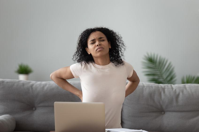 Donna al PC con mal di schiena
