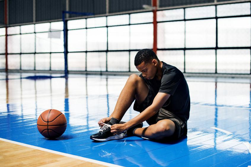 Ragazzo adolescente americano legando i lacci delle scarpe su un campo da basket