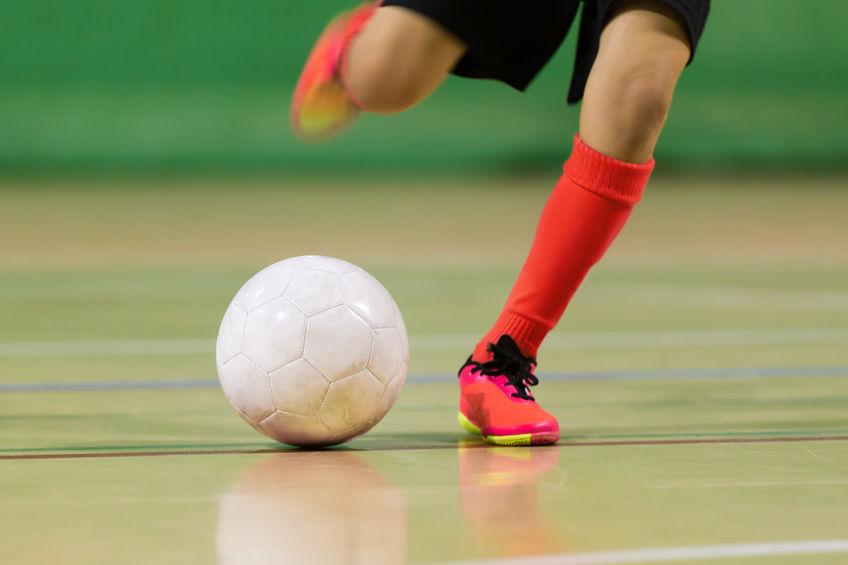 ragazzo gioca a calcio futsal di calcio nel palazzetto dello sport