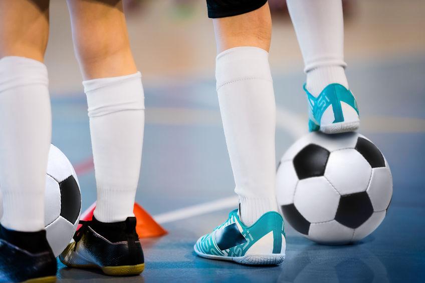tenendo un pallone da calcio con il piede