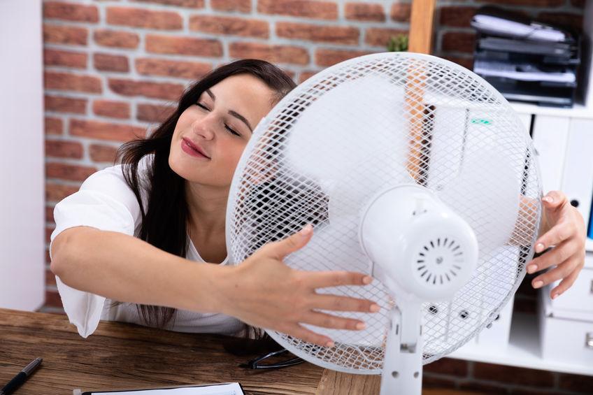 Donna che abbraccia un ventilatore