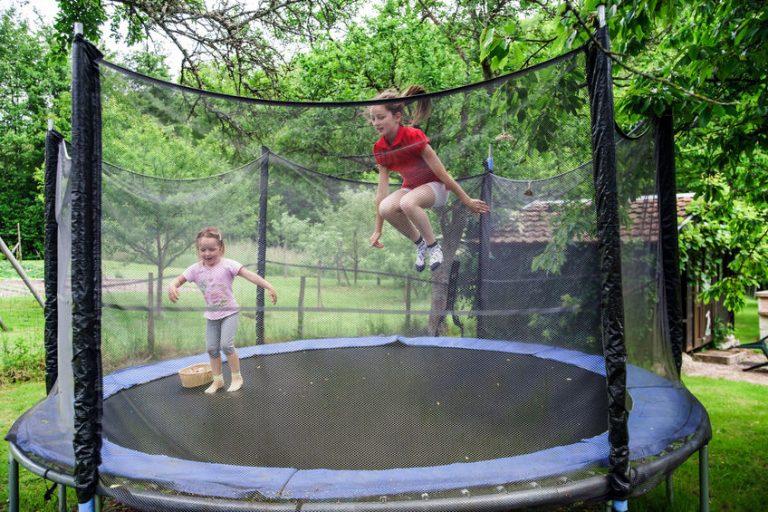 Sorelle dentro a un trampolino saltando