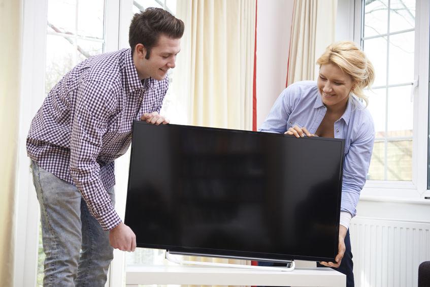Due persone che sollevano un televisore