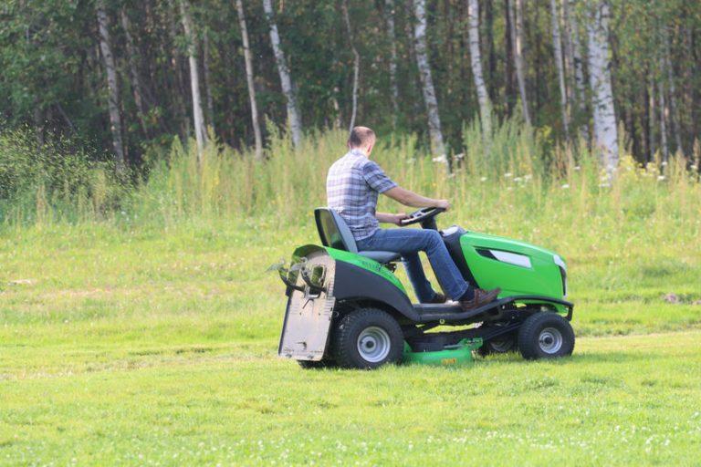Uomo che taglia l'erba con un trattorino