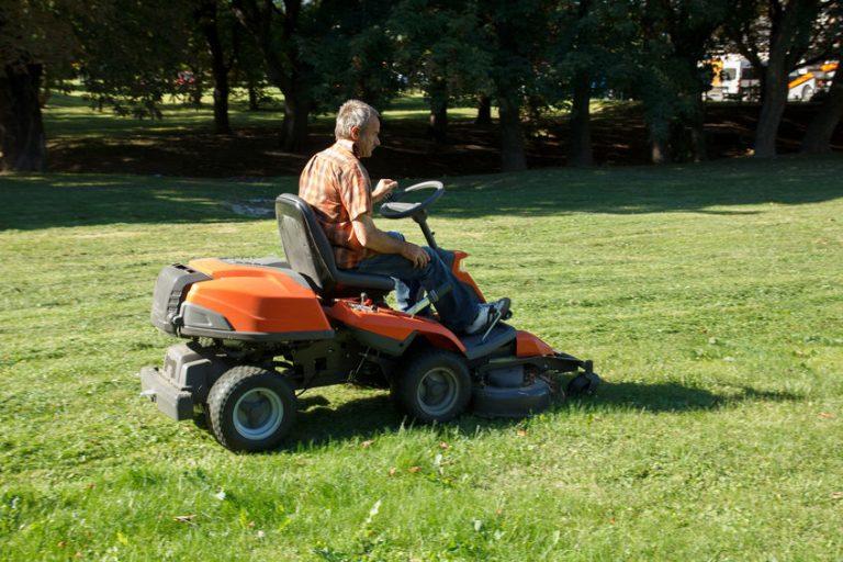 Uomo su un trattorino che taglia l'erba