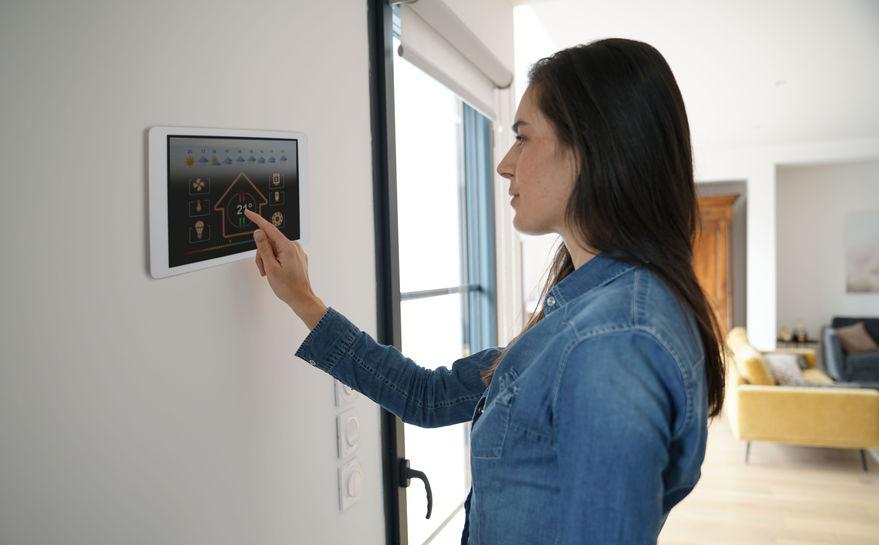 Donna che usa un termostato a parete