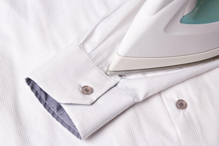 close up of iron ironing sleeve of cotton shirt