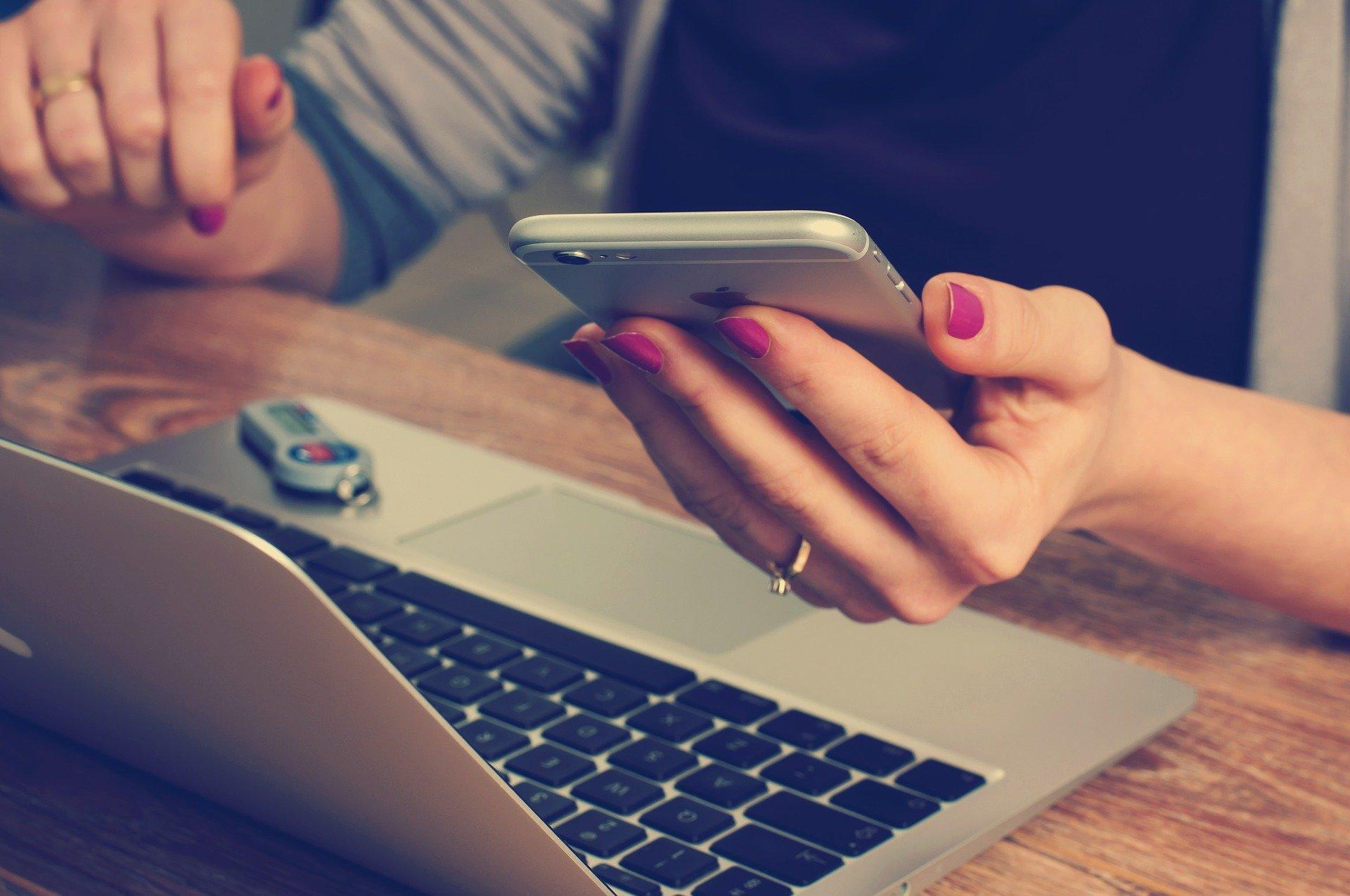 Donna con cellulare e PC portatile