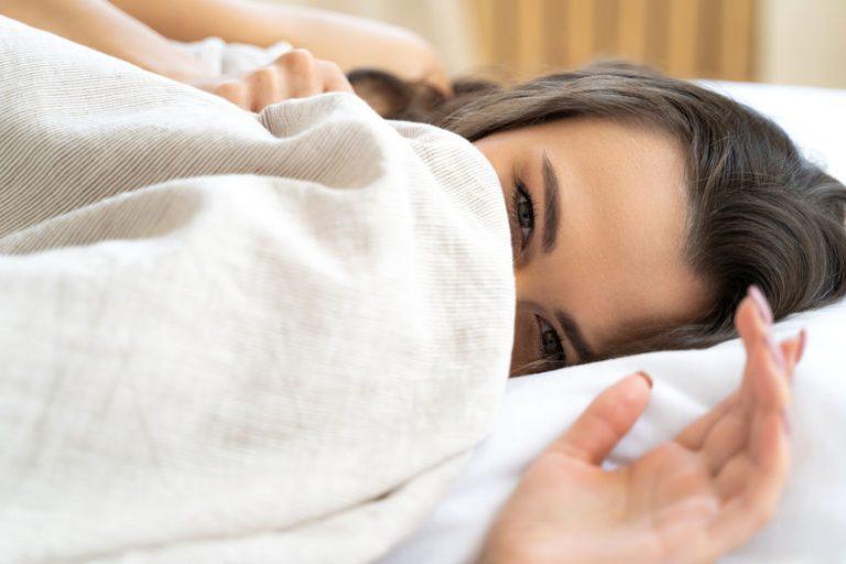 Donna sotto le lenzuola con sorrido malizioso