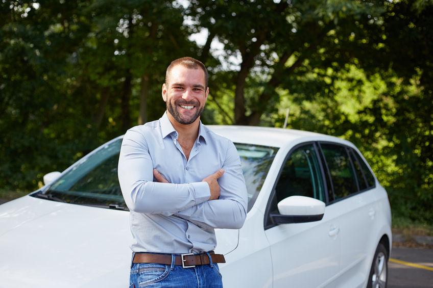 Uomo che sorride appoggiato alla macchina