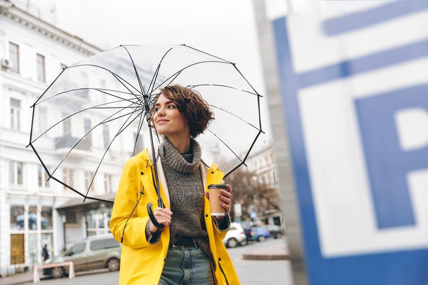 Donna giovane con impermeabile e ombrello aperto