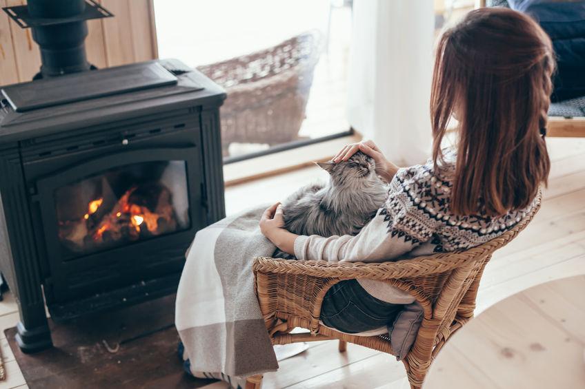 Donna con gatto in collo davanti a una stufa a legna