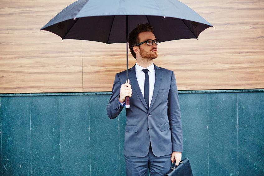 Uomo in giacca e cravatta con l'ombrello aperto
