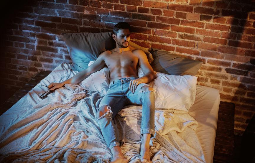 Uomo a torso nudo steso sul letto