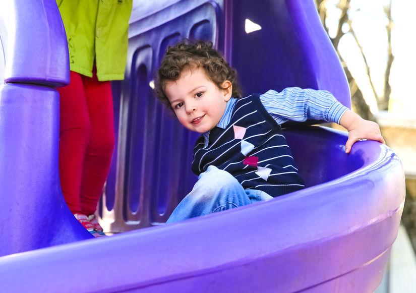 Bambino su uno scivolo viola