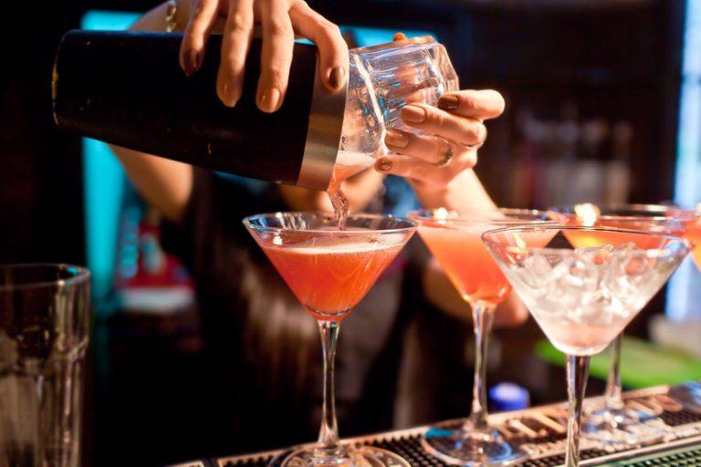 Barman che versa un cocktail in più bicchieri