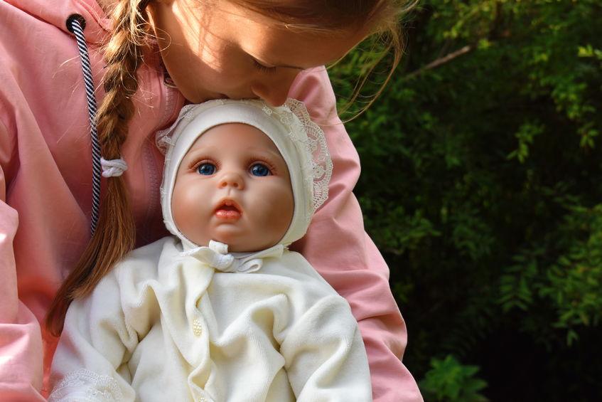 Ragazzina che bacia una bambola sulla fronte
