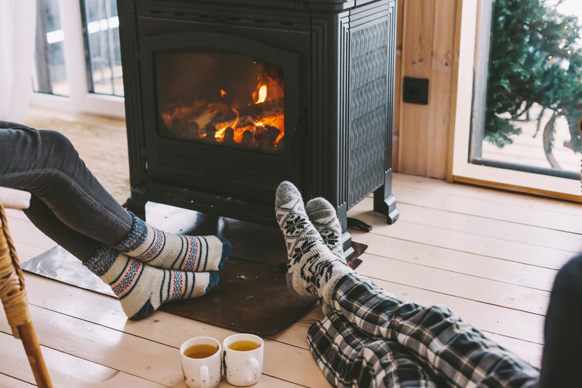 Persone che si riscaldano davanti a una stufa a legna