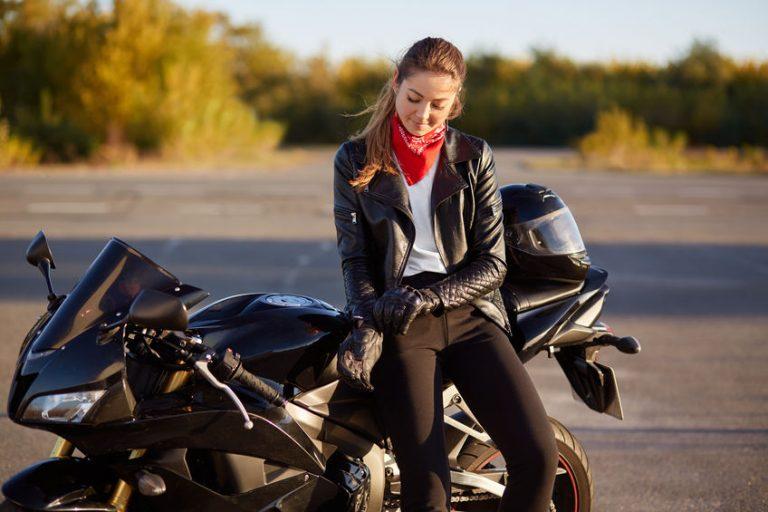 Ragazza su una moto che si infila i guanti