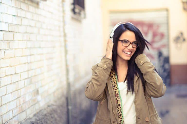 Donna che indossa le cuffie per strada