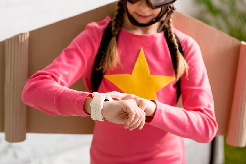 Niña con camisa rosada mirando reloj