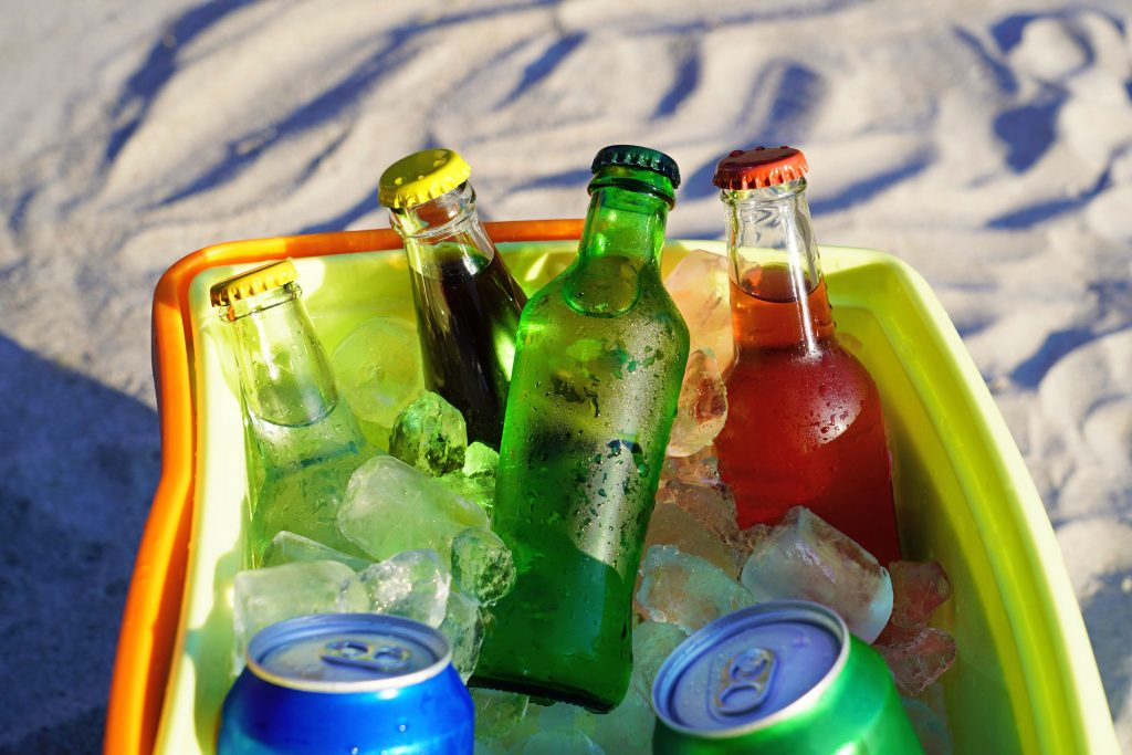 Bebidas gaseosas y cubitos de hielo llenos en una caja fría en la arena de la playa.