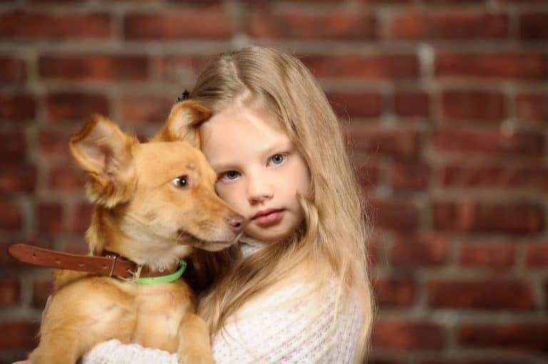 Una niña abrazando a un perro