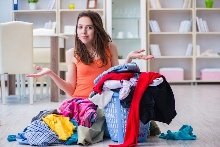 Una chica junto a un montón de ropa