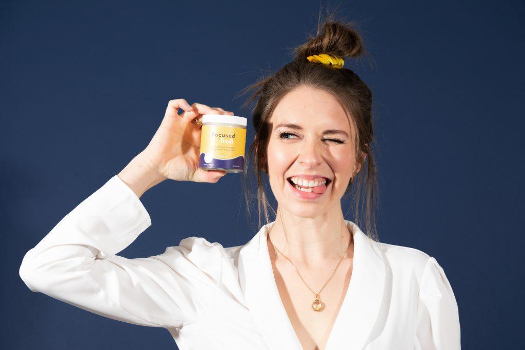 Mujer vestida de blanco sosteniendo un tarro de vitaminas
